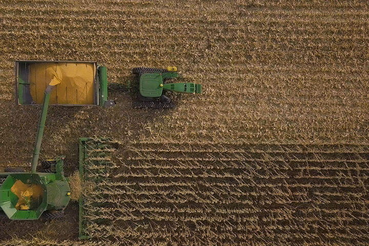 Combine emptying corn onto grain cart as seen from above